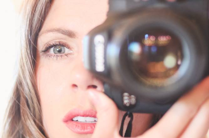 up-close image of danielle trask holding camera lens focusing with eyes fixated on client in phoenix az